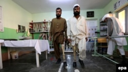 Afghan victims, who lost their limb in landmines blasts, practice with prosthetic limbs, at International Committee of the Red Cross (ICRC) center in Herat on January 31.