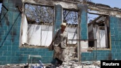 A woman searches for usable objects in a house burnt down during ethnic clashes in the city of Osh in June 2010.