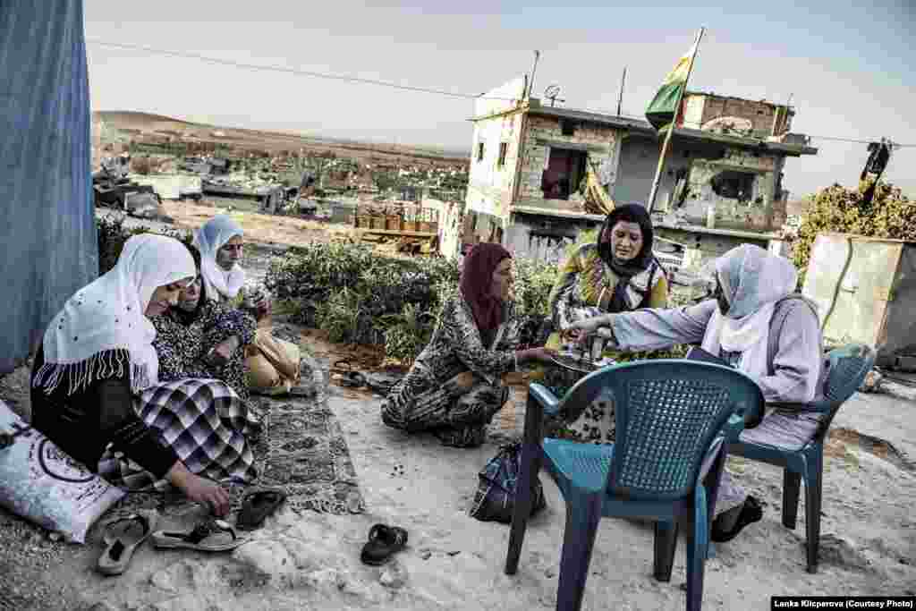 A group of women sipping tea at the top of Kobani Hill. The women live in a tent city next to their destroyed homes.