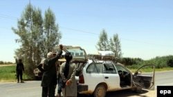 FILE: Afghan soldiers check a vehicle on a road in Helmand's Greshk district.