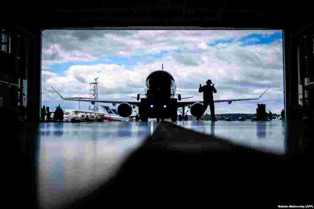 An aircraft mechanic assists to park the Embraer-175 airplane inside a hangar at the airport outside Minsk. (AFP/Maksim Malinovsky)
