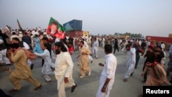 Supporters of Pakistani opposition leader Imran Khan run from tear gas as clashes begin between police and protesters in Swabi on October 31.