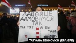 """Imagine de la un protest organizat săptămâna trecută la Minsk împotriva unificării Belarusului cu Rusia. """"Să cădem astfel de acord - noi suntem aici, iar voi, dincolo"""", scrie pe pancarta unei protestatare"""