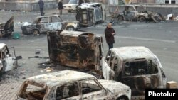 Armenia - A man walks past burned cars on a street in Yerevan where security forces clashed with opposition protesters, 2 March 2008.