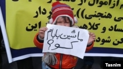 "Victims of financial institutions during a protest in Tehran. The child hold a placard saying, ""Where is my daddy's car""."