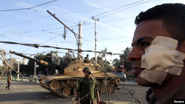 An anti-Morsi protester who was injured during clashes on November 5 with members of the Muslim Brotherhood, stands near a barbed wire barricade in front of the presidential palace in Cairo.