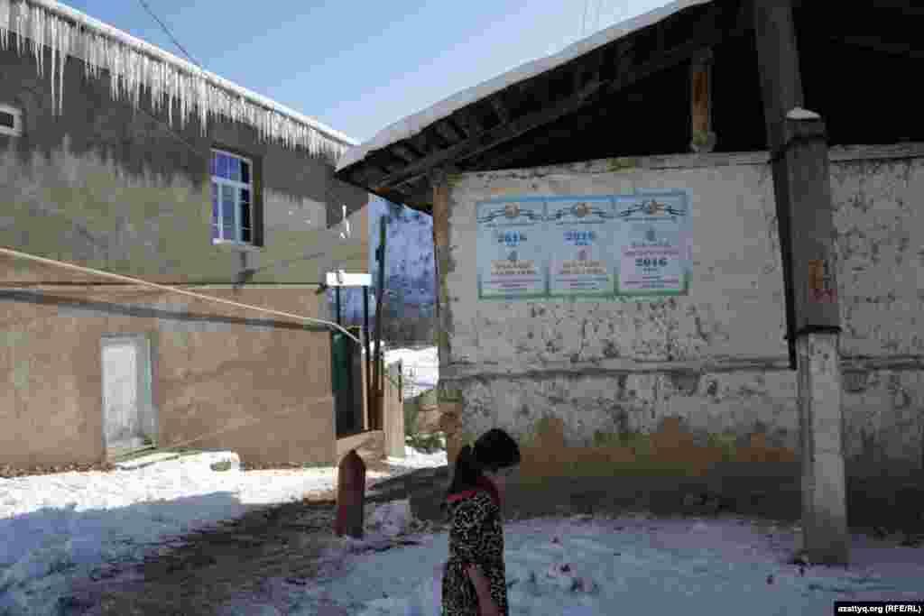 Девочка проходит мимо здания, на стене которого размещены плакаты о предстоящих выборах президента Узбекистана. Ташкентская область, 27 ноября 2016 года.