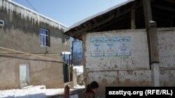 Divarına prezident seçkiləri barədə plakatlaryapışdırılmış tikilinin yanından keçən qız. Daşkənd vilayəti, 27 noyabr 2016-cı il.
