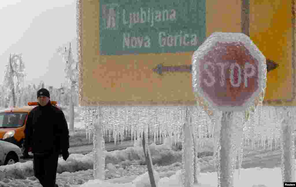 A man walks next to ice-covered road signs in Postojna, Slovenia, on February 3. (Reuters/Srdjan Zivulovic)