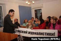 Пристав административного суда города Алматы рвёт плакат со словами протеста журналистов оппозиционной газеты. Алматы, 7 февраля 2013 года.