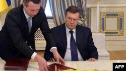Виктор Янукович подписывает соглашение, которое он не хотел бы подписывать