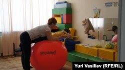 Церебралды сал ауруына шалдыққан балаларды оңалту орталығында науқас баламен жұмыс істеп жатқан адам. (Көрнекі сурет.)