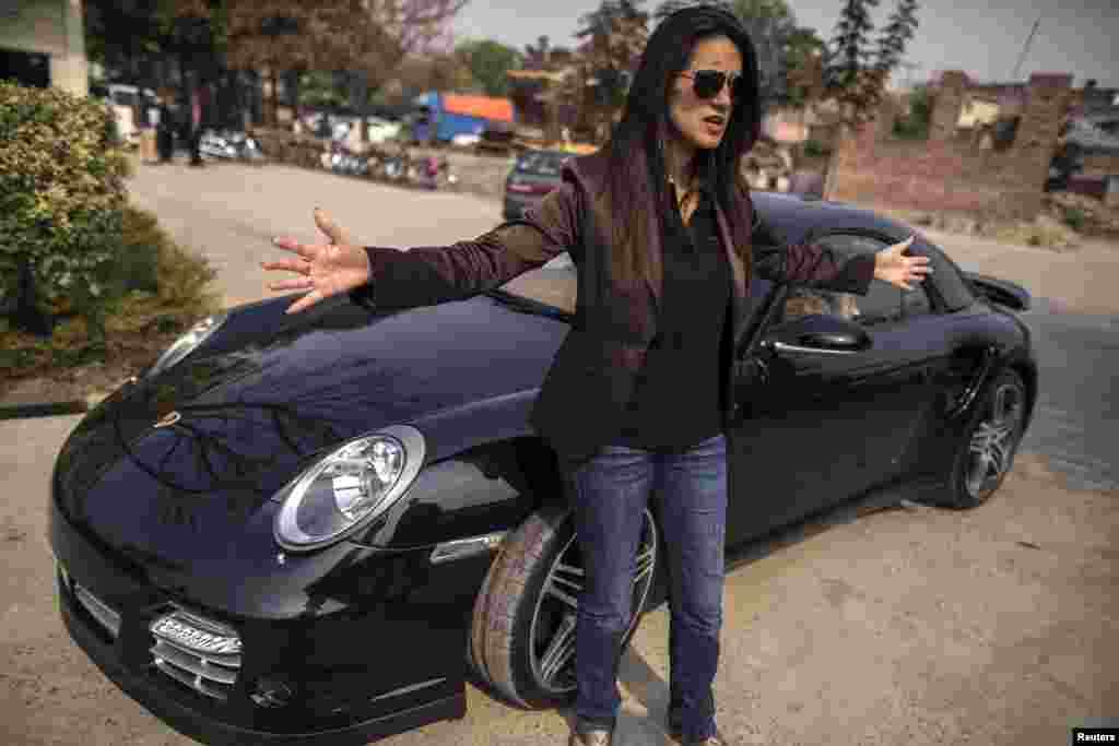 Ansa Hasan, a marketing manager at Porsche Pakistan, gestures outside the Porsche showroom in Lahore as she prepares for an upcoming event.
