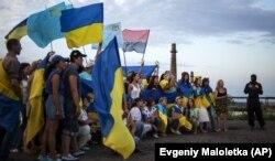 Молоді люди під час флешмобу на підтримку армії України неподалік міста Ізюм, що на Харківщині, 12 липня 2014 року