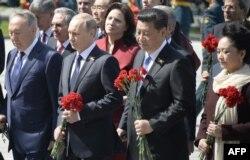 Президент Казахстана Нурсултан Назарбаев, президент России Владимир Путин, президент Китая Си Цзиньпин и его жена Пенг Люян на церемонии возложения цветов к Могиле Неизвестного Солдата. Москва, 9 мая 2015 года.
