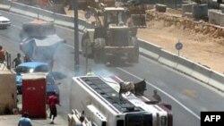 یک اتوبوس بر اثر حمله بولدوزر واژگون شد. (عکس:AFP)