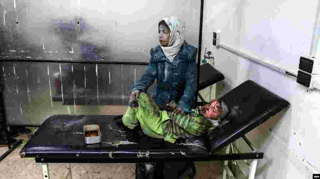 A Syrian woman sits with an injured child at a hospital following a reported strike by government forces in the rebel-held district of Barzah, on the northeastern outskirts of the capital Damascus on February 20. (epa/Sarieh Abu Zaid)