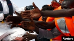Libya - Migrants reach out to grab hold of Migrant Offshore Aid Station (MOAS) rescuers on a RHIB (Rigid-hulled inflatable boat) before being taken to the MOAS ship MV Phoenix some 20 miles (32 kilometres) off the coast of Libya, August 3, 2015