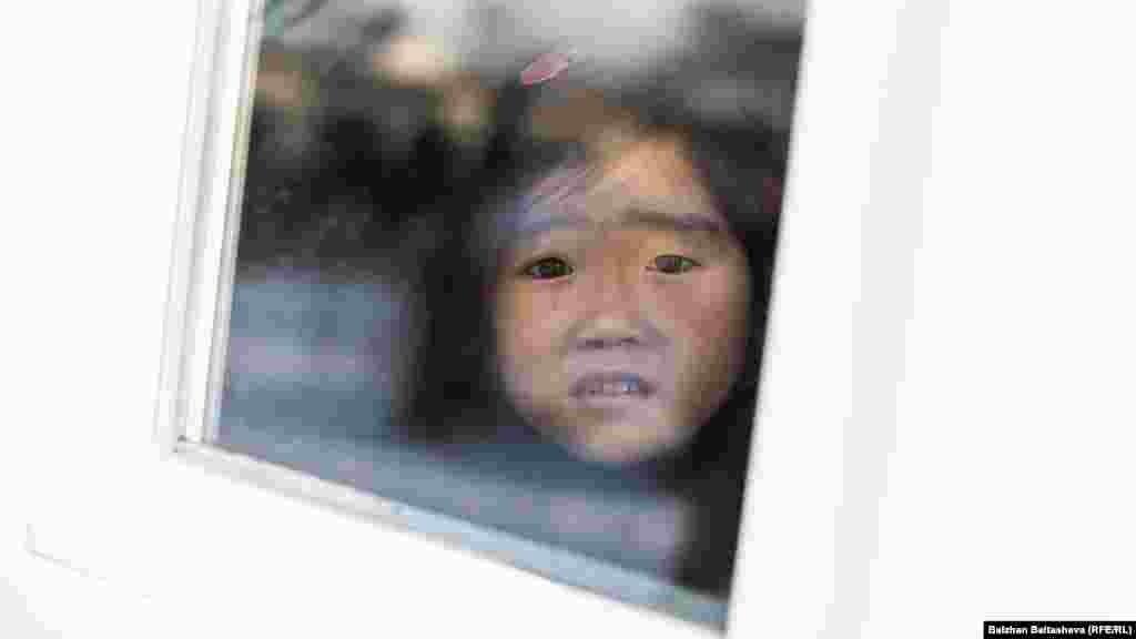 Девочка - дочь Салтанат Куатовой - смотрит через окно.