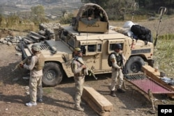 FILE: Members of Afghan security forces take positions during an operation against IS militants.