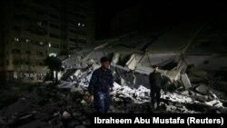 Palestinski policajac pored porušene zgrade u Gazi 11. maja 2021. godine