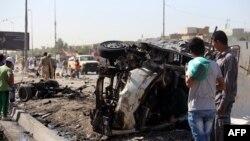 Njerëzit e tubuar në vendin e një shpërthimi të mëparshëm në lagjen Sadr City të Bagdadit në Irak