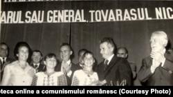Nicolae Ceauşescu îi dă Nadiei Comăneci titlul de Erou al Muncii Socialiste şi medalia de aur Secera şi Ciocanul (19 august 1976). Sportiva fuge din țară la sfârșitul lunii noiembrie 1989. Sursa: Fototeca online a comunismului românesc. Cota: 168/1976