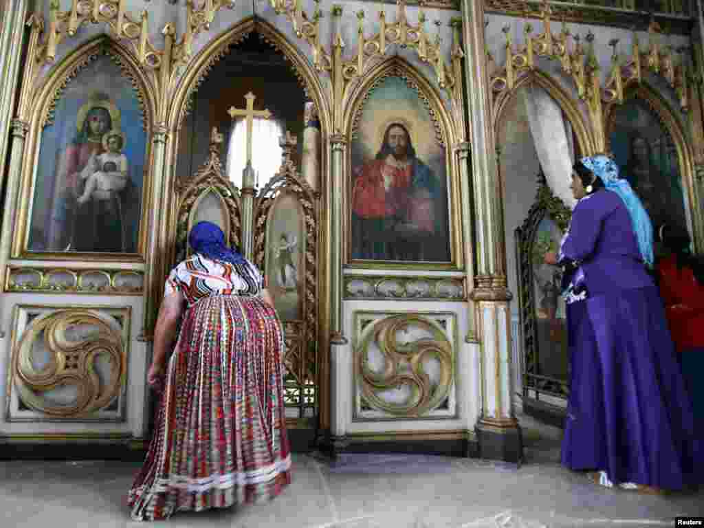 Two Romany women pray inside an Orthodox church during the gathering of the Romany minority in Costesti, Romania, on September 8. (Photo by Radu Sigheti for Reuters)