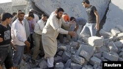 Syria -- Men search for bodies under rubble of a house, destroyed by a government Air force air strike, in a village of Tel Rafat, about 37 km north of Aleppo, 08Aug2012