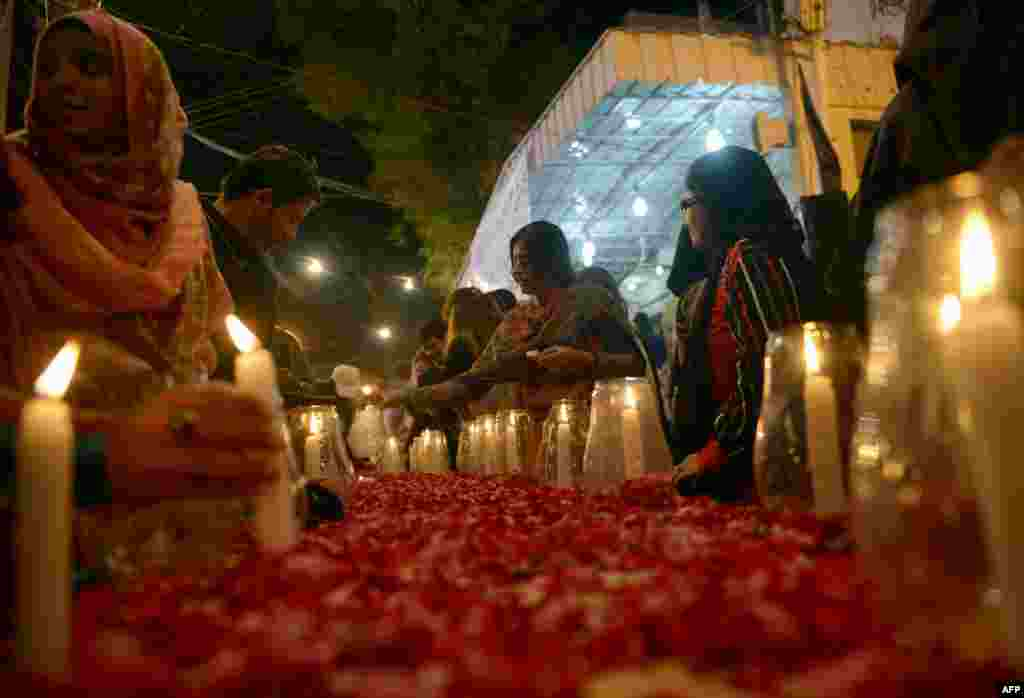 Pakistani female activists from the Muttahida Qaumi Movement (MQM) light candles in Karachi for the 141 victims of the Taliban attack in Peshawar on December 16. (AFP/Rizwan Tabassum)