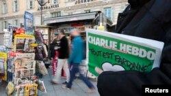 Мужчина держит в руках первый после атаки на редакцию выпуск журнала Charlie Hebdo. 14 января 2015 года.
