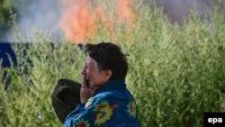 Жінка плаче поряд з її будинком, який був зруйнований під час бойових дій у Слов'янську, 30 червня 2014 року