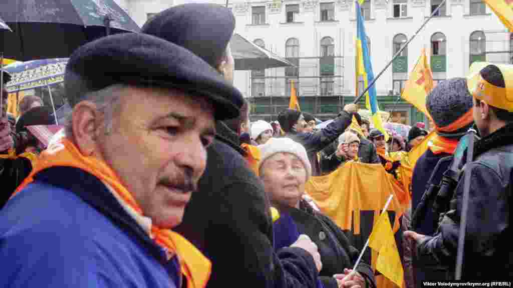 Ukraina tarafdarları, Yuşçenkonıñ saylav kampaniyasınıñ timsalâtınen portaqal tüslü bayraqlarnı, ve ukran ve qırımtatar bayraqlarnı tuta.