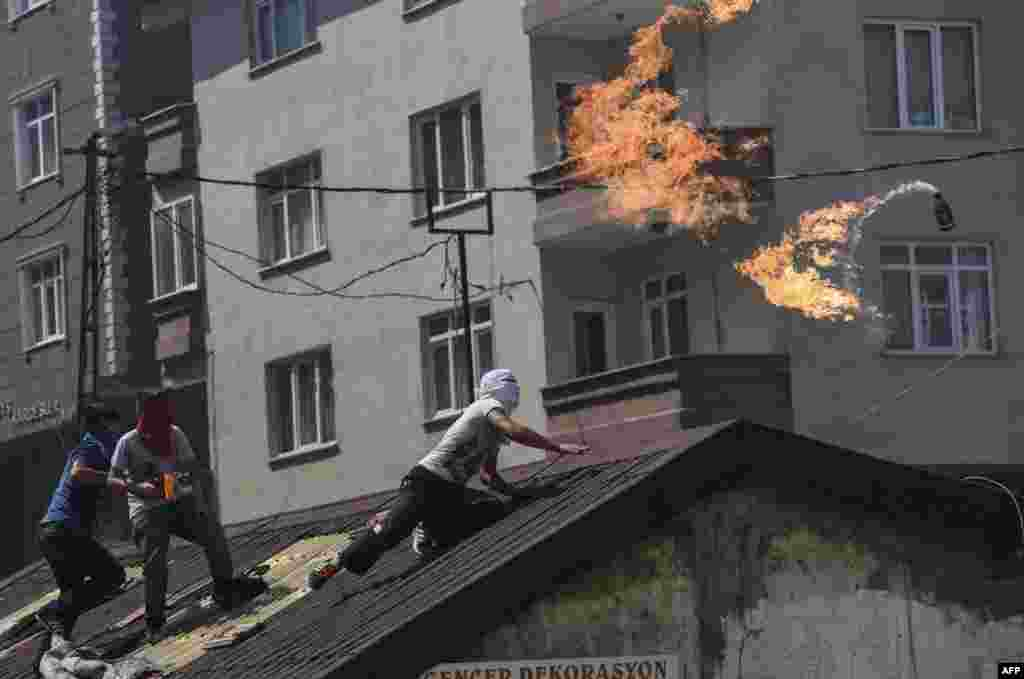 A left-wing militant throws a Molotov cocktail during clashes with Turkish riot police in Istanbul's Gazi district. (AFP/Bulent Kilic)