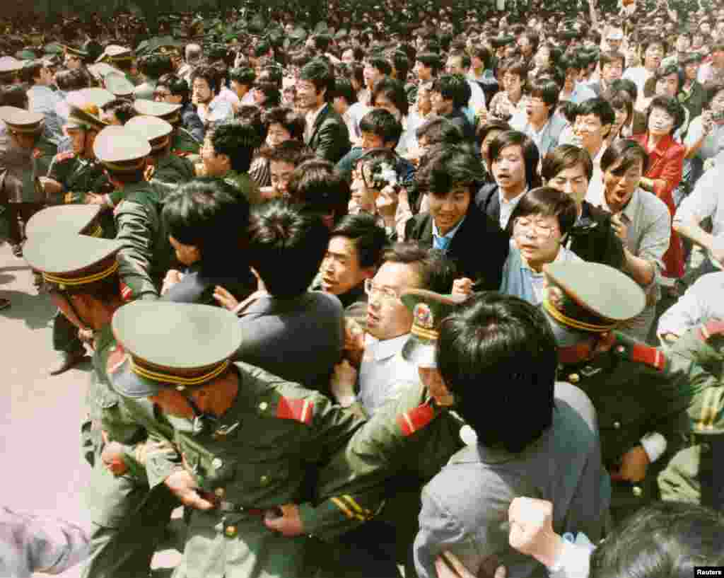 Crowds of students surge through a police cordon to reach Tiananmen Square, which had been blocked by security forces on June 3 and 4.