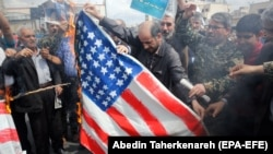 Protesters burn U.S. flag as they take part in an anti-U.S. rally after Friday Prayers to show their support of Iran's revolutionary guards corps (IRGC), in Tehran, April 12, 2019