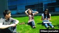 ЖОО ғимараты жанында отырған қазақстандық студенттер. (Көрнекі сурет)