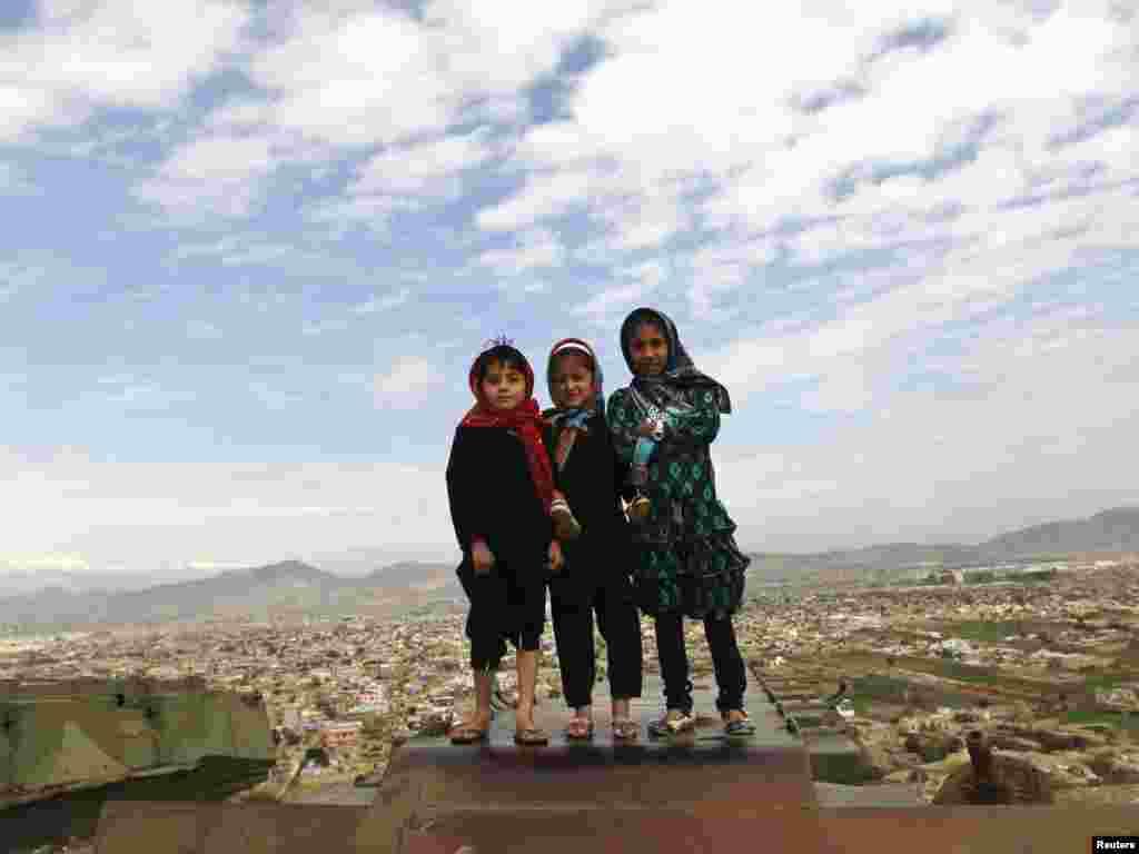 Kabulda dağıdlımış zirehli maşının üzərinə çıxıb şəkil çəkdirən əfqan qızlar. (Foto: Omar Sobhani/Reuters)