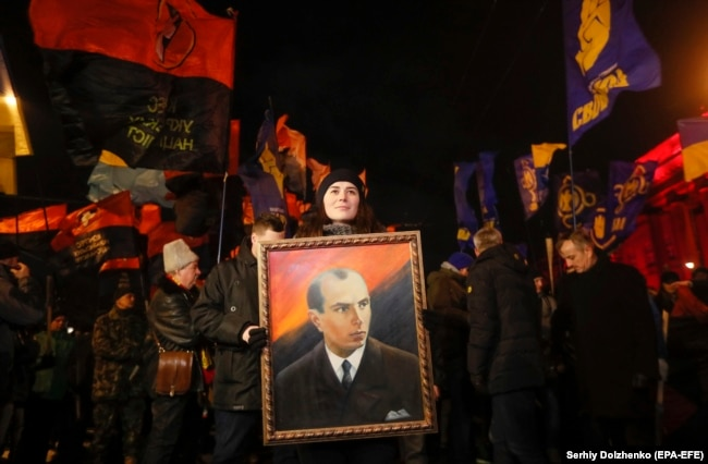 A woman holds a Stepan Bandera portrait during a rally of different nationalist parties to mark the 110th anniversary of his birth in Kyiv on January 1.