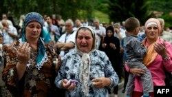 Босниялык мусулман аялдар жаңы табылган сөөктөр салынган табыттарды жүктөп бараткан машинелерди карап дуба кылышууда. Високо шаарчасы. 9-июль 2015