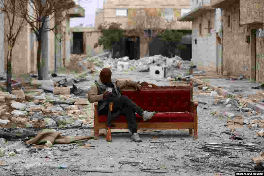 A fighter for the Turkey-backed Free Syrian Army sits in the street in the eastern suburbs of Al Bab. (Reuters/Khalil Ashawi)