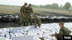 Guards at the Tajik-Afghan border sort seized heroin.