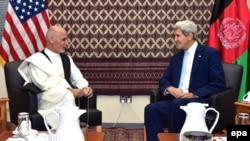 A handout picture released by the US Department of State shows US Secretary of State John Kerry (R) sits with Afghan presidential candidate Ashraf Ghani (L) in Kabul, 7 August 2014.