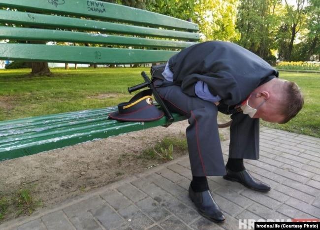 Милиционер сидит на скамейке после инцидента на Советской площади в Гродно