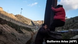 Мигранты из центральноамериканских стран пытаюсь преодолеть пограничное заграждение рядом с мексиканским городом Тихуана.