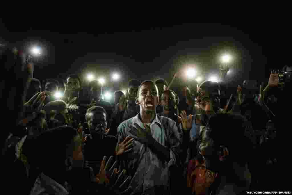 Молодий чоловік освітлений мобільними телефонами декламує протестну поезію, в той час як демонстранти скандують гасла. Хартумі, Судан, 19 червня 2019 року. Фото року World Press Photo: Переможець – Ясуйоші Чіба,Агенція«Франс-Прес»