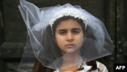 A young actress plays the role of a child bride during a protest organised by Amnesty International to denounce child marriage, on October 27 in Rome.