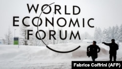 SWITZERLAND -- A security guard show the way to a man outside of the Davos Congress Centre under snow ahead of the opening of the World Economic Forum (WEF) 2018 annual meeting, in Davos, January 22, 2018