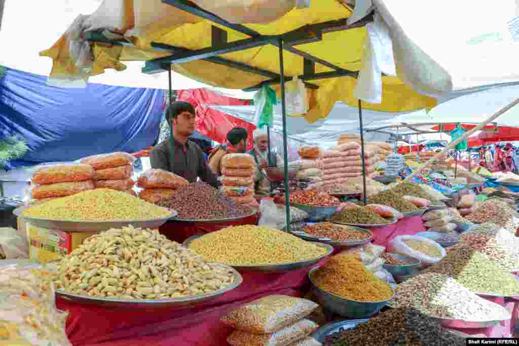 Shopkeepers sell sweets and dried fruit to customers in Kabul's Pule Baghe Omomi open-air market.