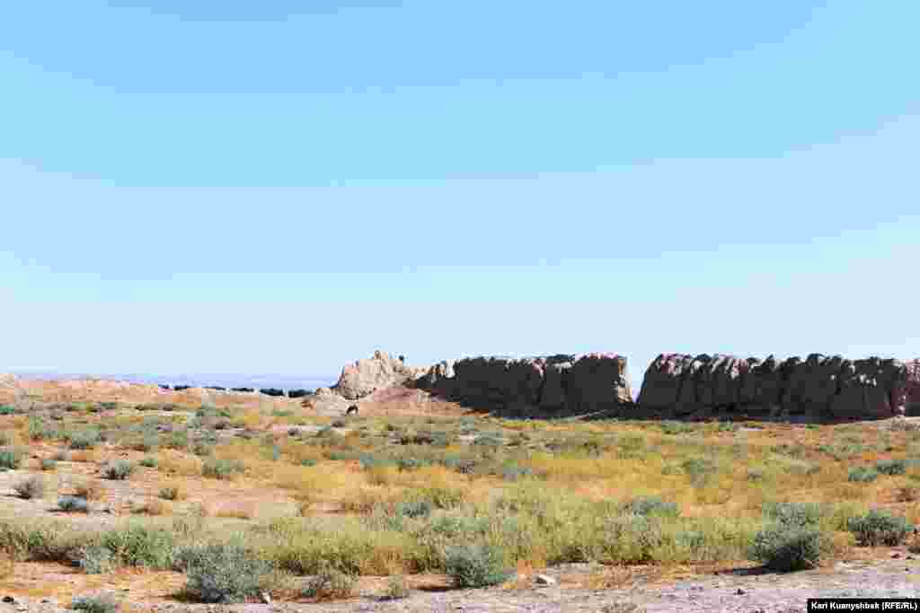 Қамал қабырғаларының бірінің ішінен қарағандағы көрініс. Қорған сыртында мұнай өнімдерін артқан жүк составы кетіп барады.